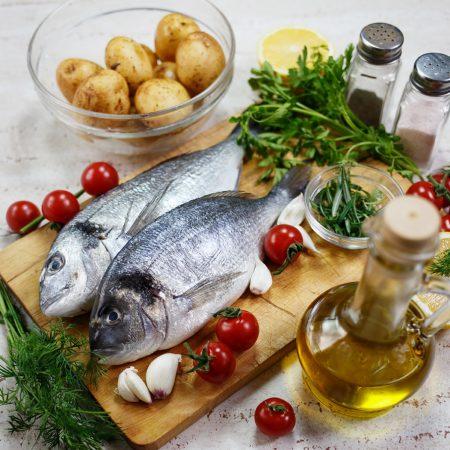 Dorada pieczona na młodych ziemniakach, z pomidorami, cytryną i rozmarynem
